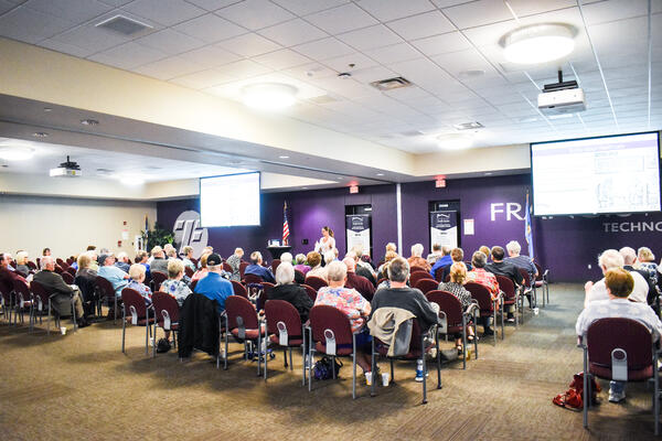 Nikki Buckelew presents to a large crowd at a free series on senior living.