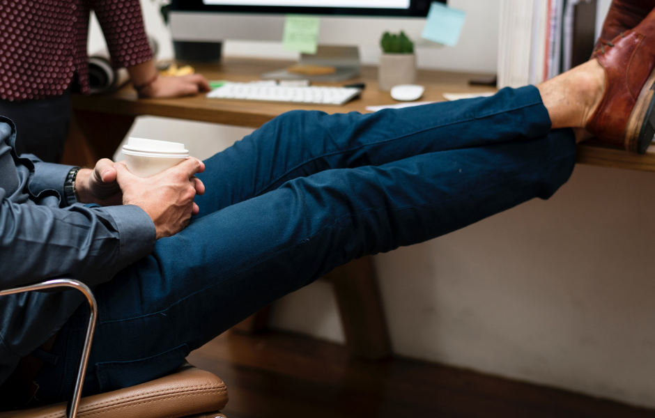 person leaning in chair with feet on desktop
