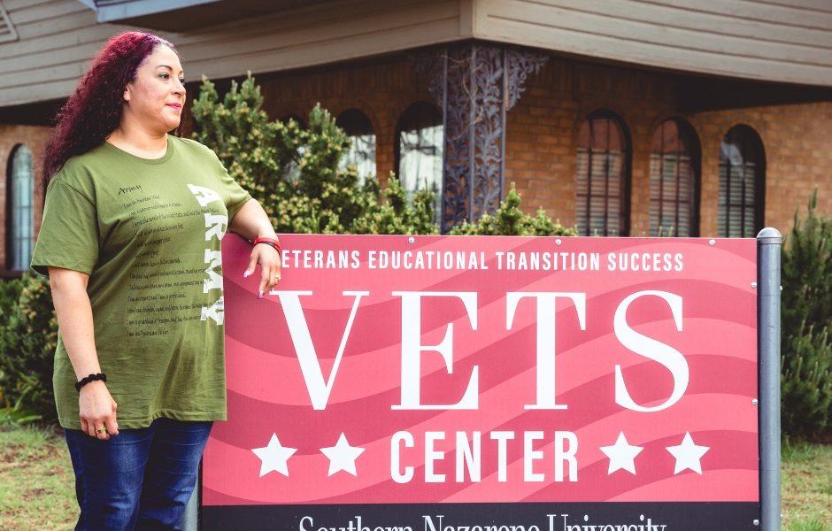 Army Veteran standing beside SNU VETS Center sign