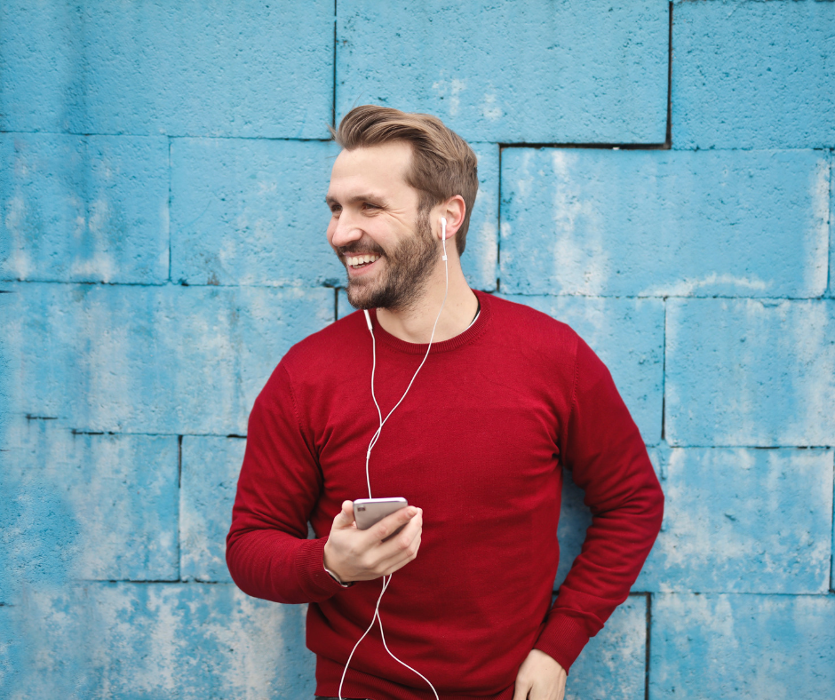 person smiling, standing against blue wall