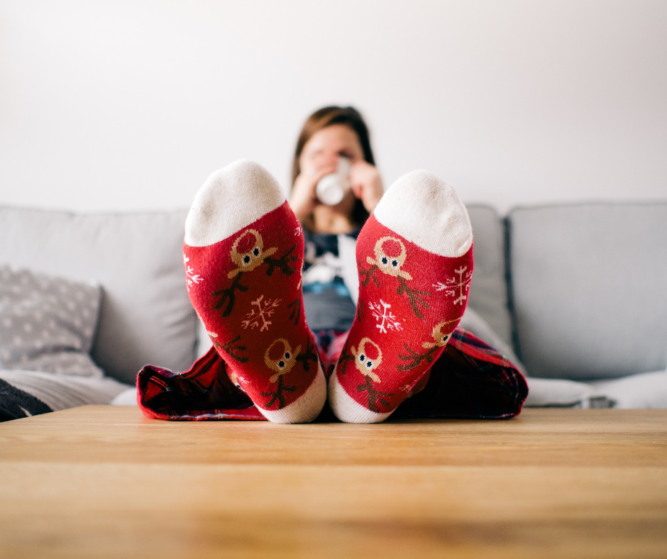 woman wearing Christmas socks while sitting on couch