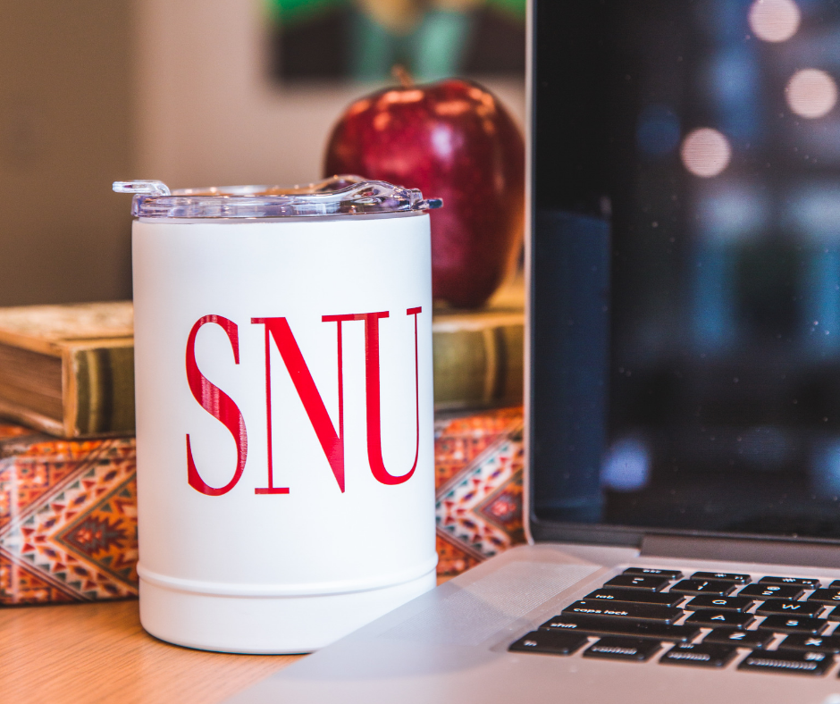 SNU mug next to laptop computer