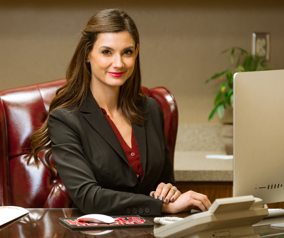 woman sitting behind desk smiling