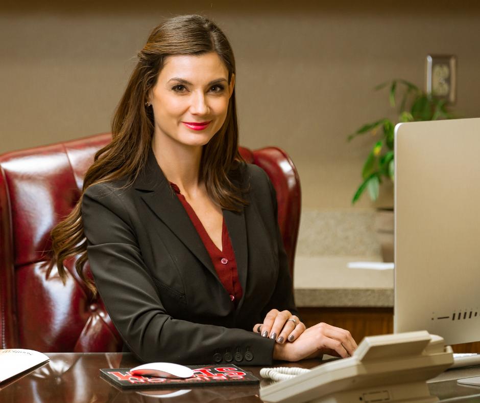 woman sitting behind desk smiling