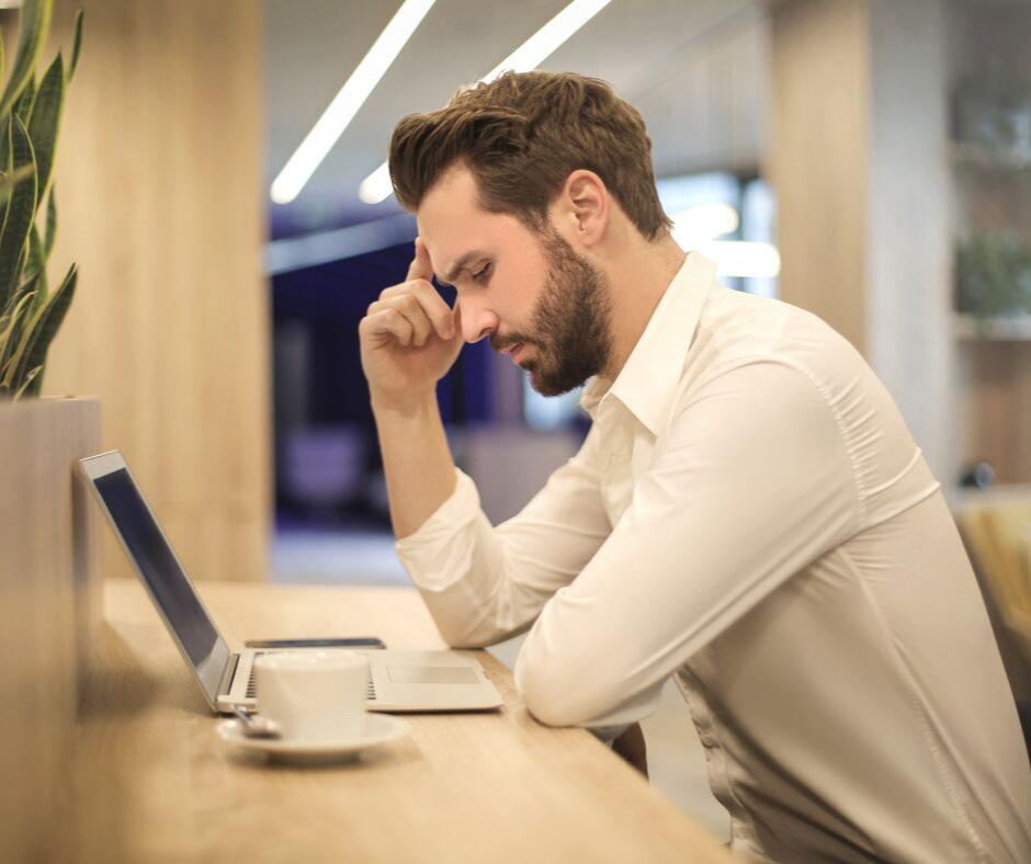 man sitting at counter on laptop