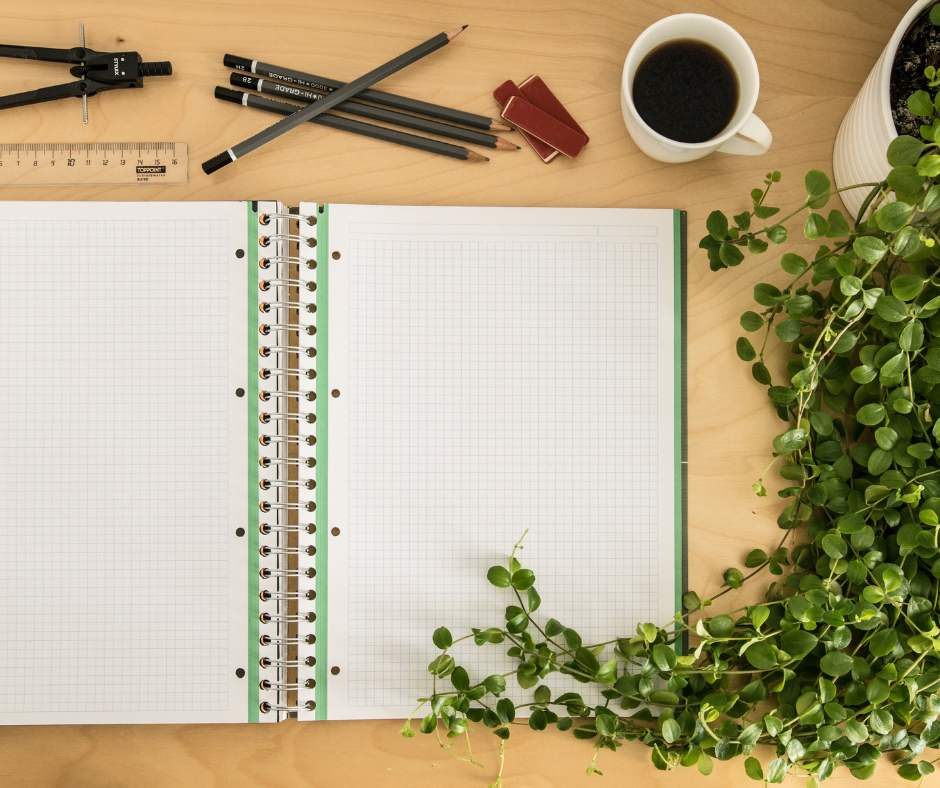 empty notebook surrounded by pencils and plant