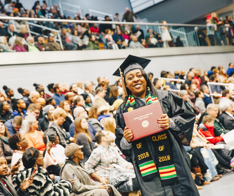 woman at graduation, smiling, holding diploma